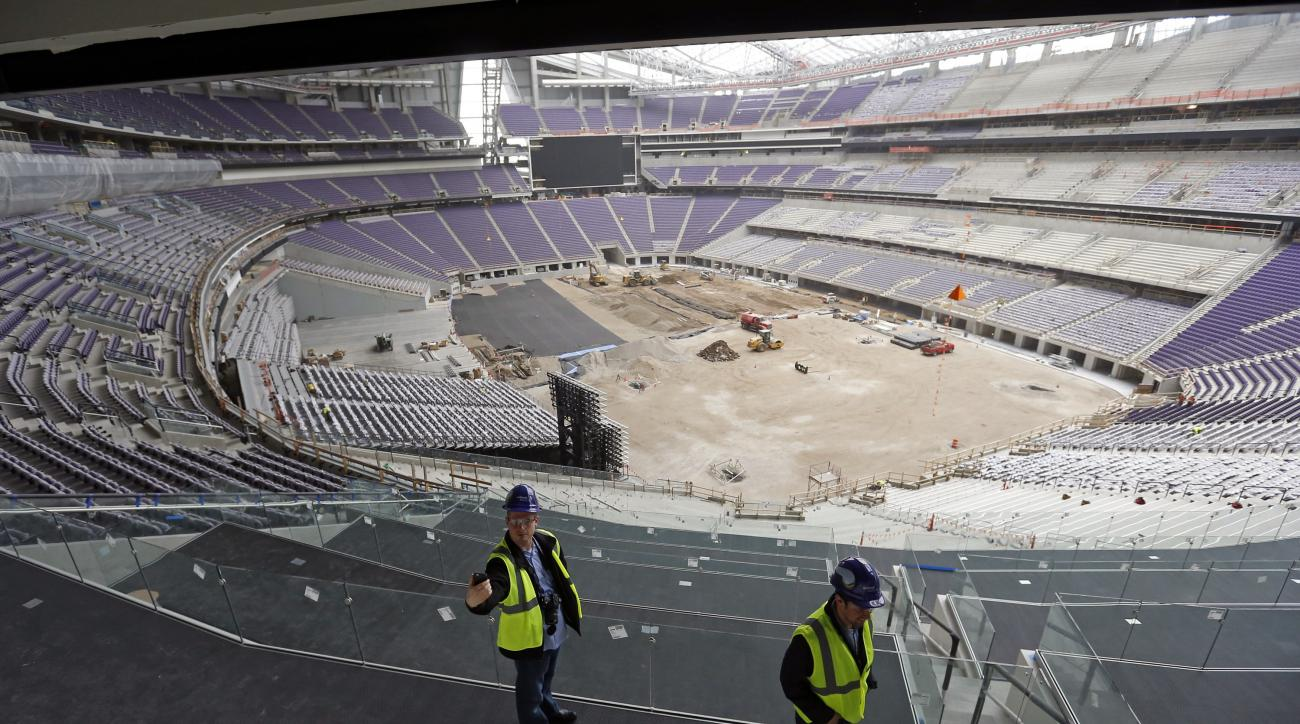 FILE - In this Feb. 16, 2016, file photo, a member of the media, left, takes a photo during a tour of the new U.S. Bank stadium which will be home to the Minnesota Vikings NFL football team in Minneapolis. Workers are putting finishing touches on the new,