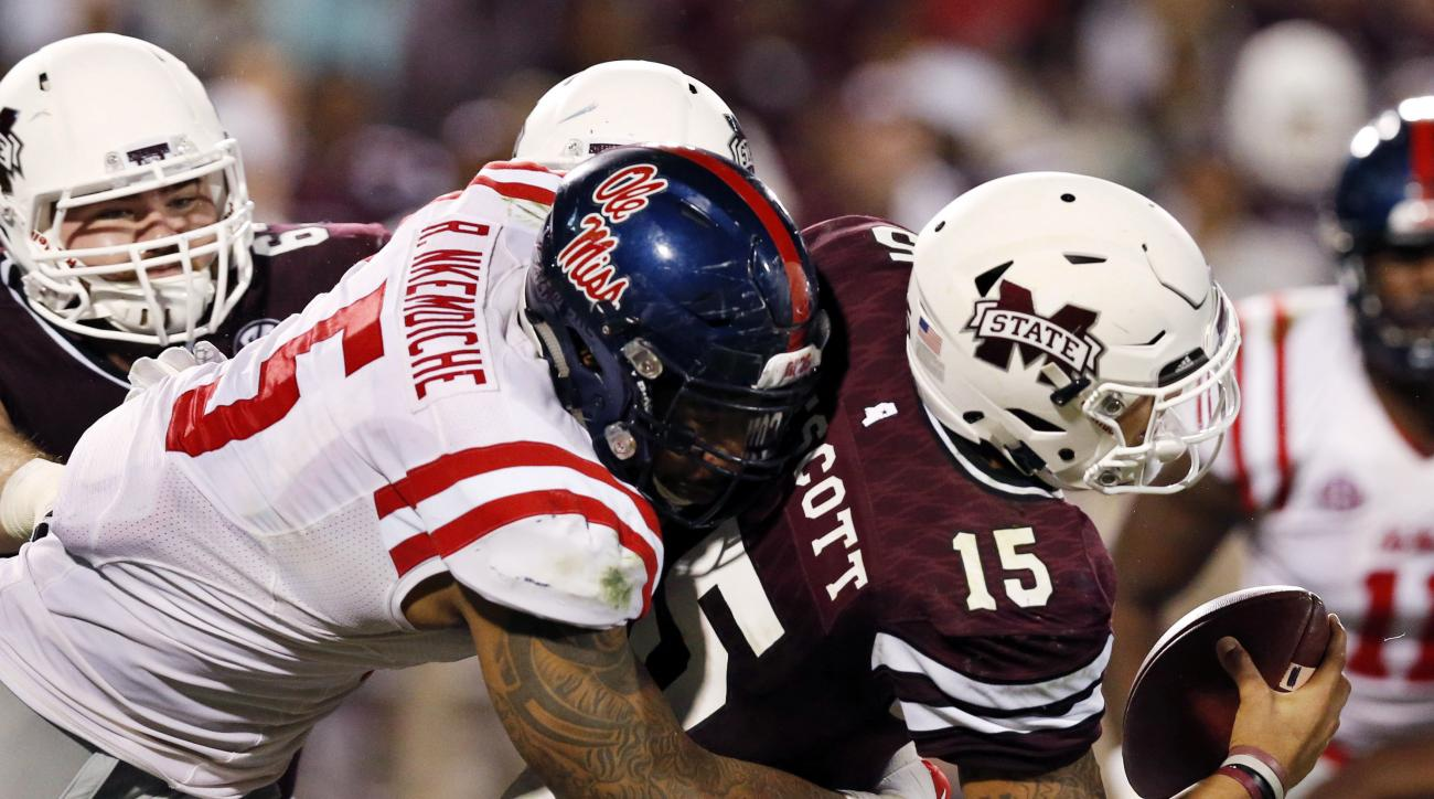 FILE - In this Nov. 28, 2015, file photo, Mississippi State quarterback Dak Prescott (15) is sacked by Mississippi defensive tackle Robert Nkemdiche (5) in the second half of an NCAA college football game in Starkville, Miss. Nkemdiche is one of the top d