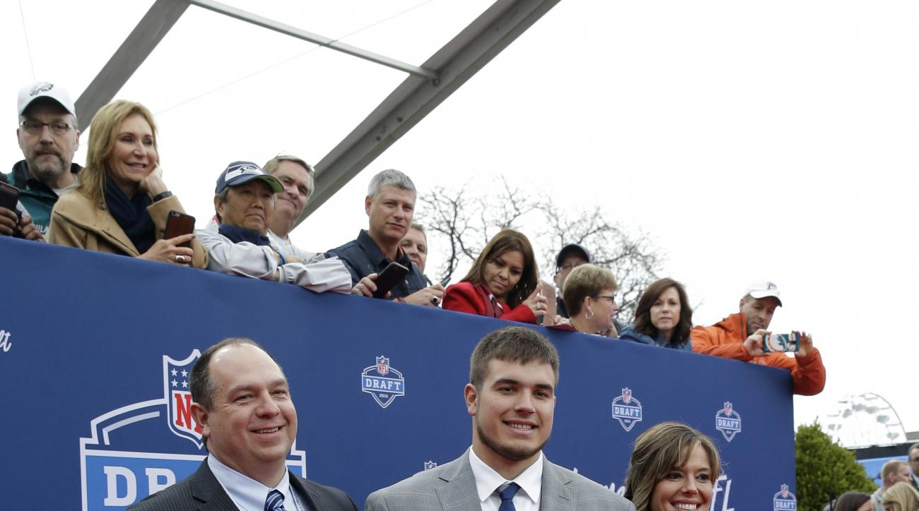 Michigan States Jack Conklin, center, poses for photos upon arriving for the first round of the 2016 NFL football draft at the Auditorium Theater of Roosevelt University, Thursday, April 28, 2016, in Chicago. (AP Photo/Nam Y. Huh)