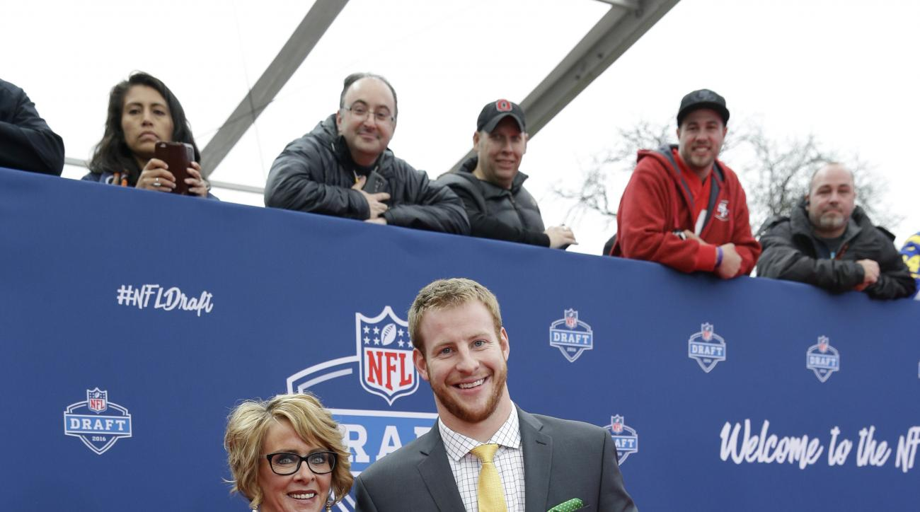 North Dakota States Carson Wentz, right, poses for photos upon arriving for the first round of the 2016 NFL football draft at the Auditorium Theater of Roosevelt University, Thursday, April 28, 2016, in Chicago. (AP Photo/Nam Y. Huh)