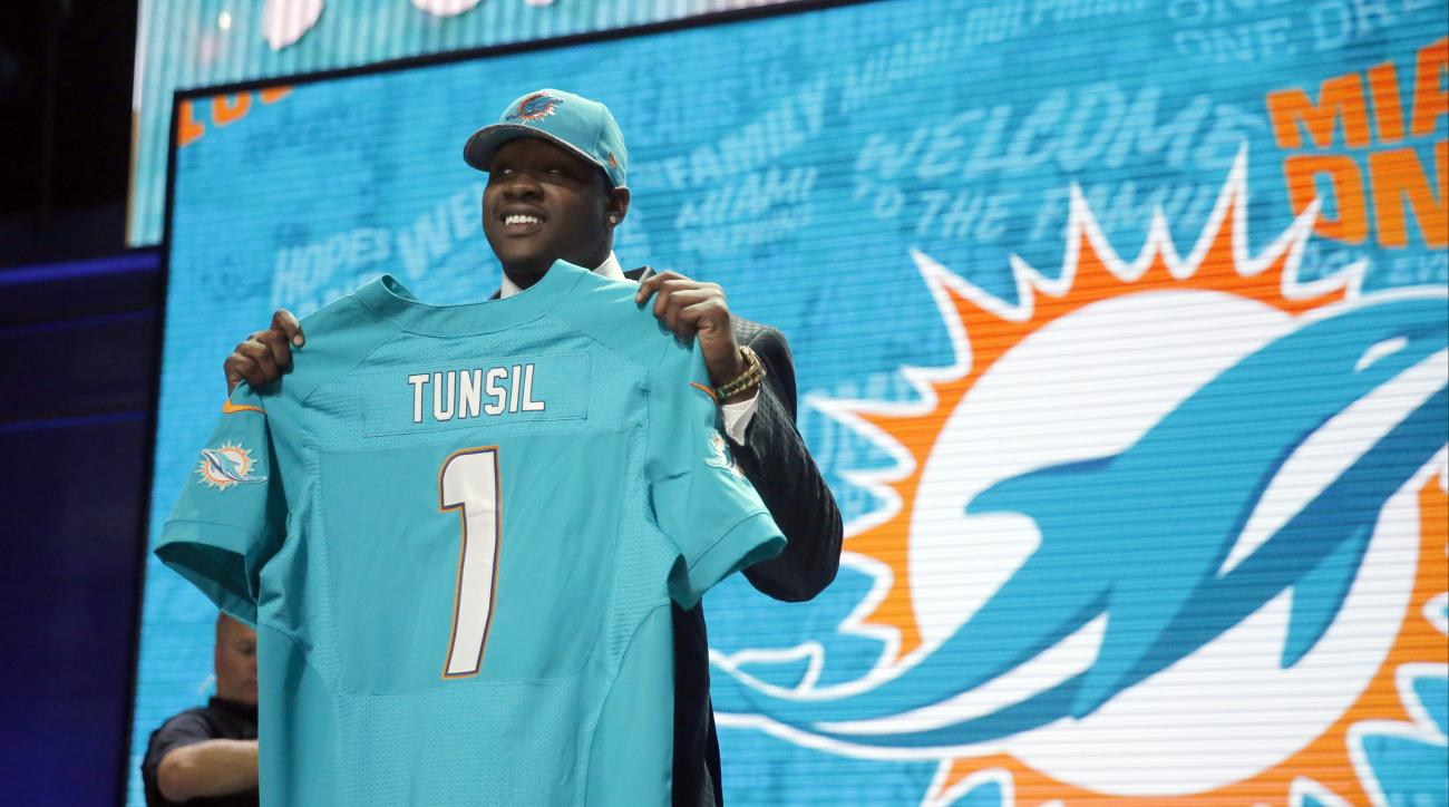 Mississippis Laremy Tunsil poses for photos after being selected by the Miami Dolphins as the 13th pick in the first round of the 2016 NFL football draft, Thursday, April 28, 2016, in Chicago. (AP Photo/Charles Rex Arbogast)