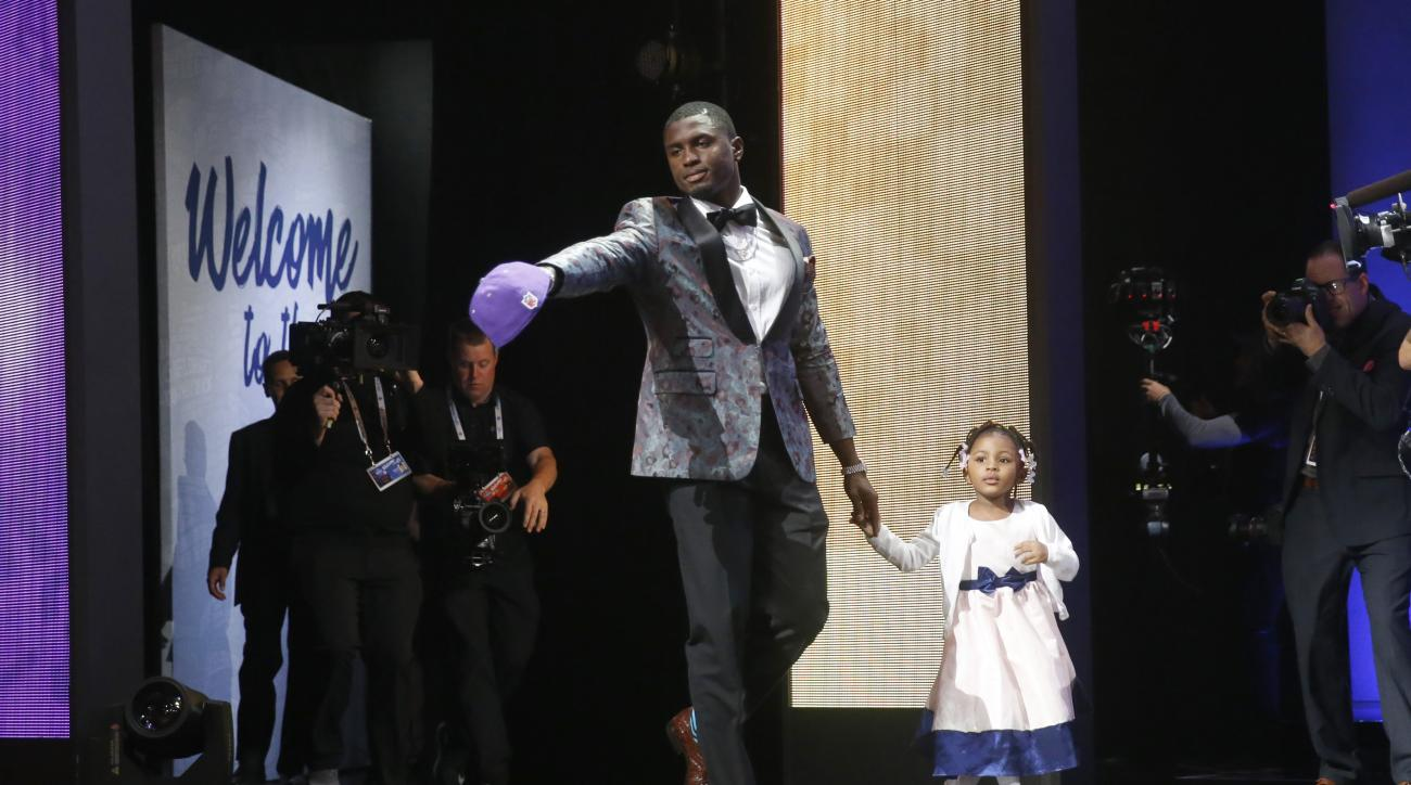 Mississippis Laquon Treadwell walks on the stage with his daughter Madison after being selected by the Minnesota Vikings as the 23rd pick in the first round of the 2016 NFL football draft, Thursday, April 28, 2016, in Chicago. (AP Photo/Charles Rex Arboga