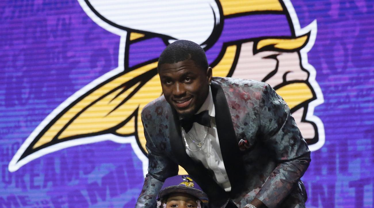 Mississippis Laquon Treadwell poses for photos with his daughter Madison after being selected by the Minnesota Vikings as the 23rd pick in the first round of the 2016 NFL football draft, Thursday, April 28, 2016, in Chicago. (AP Photo/Charles Rex Arbogast
