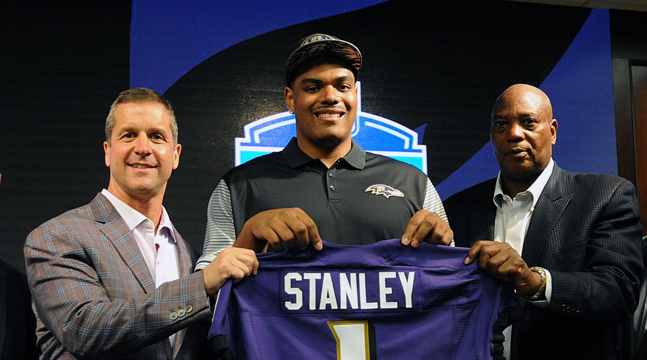 Baltimore Ravens first round draft pick Ronnie Stanley, center, holds up his jersey with head coach John Harbaugh, left, and general manager Ozzie Newsome, before a news conference Friday, April 29, 2016, in Owings Mills, Md. (AP Photo/Gail Burton)