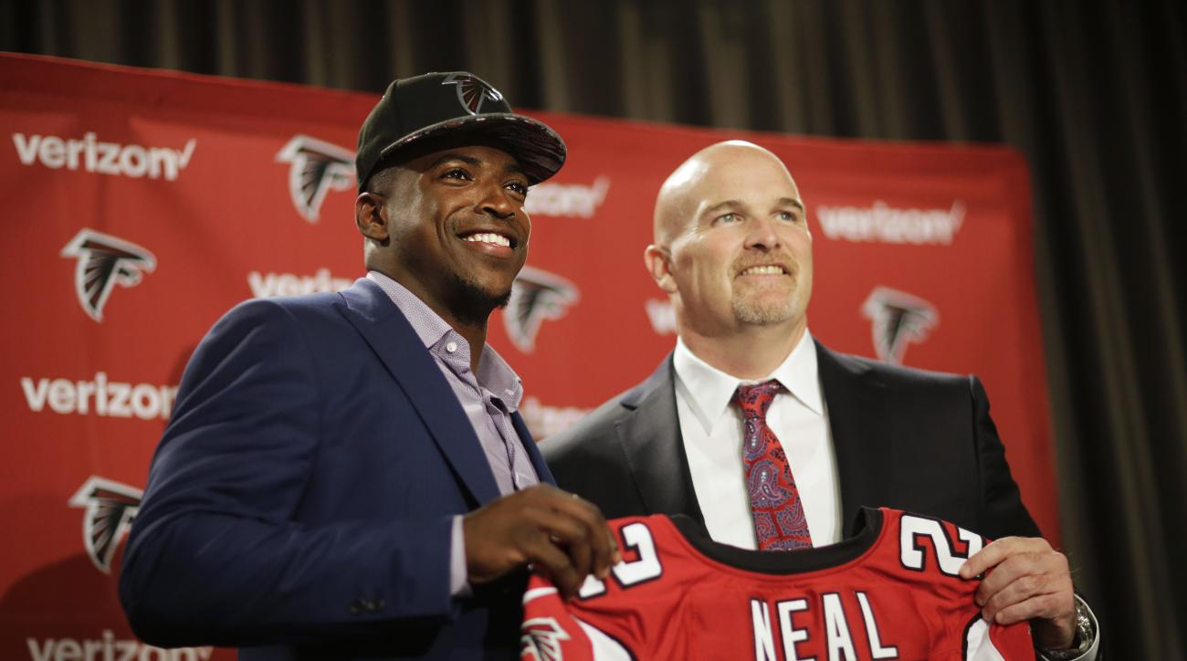 Atlanta Falcons first-round draft pick Keanu Neal, left, poses for a photo with his jersey and head coach Dan Quinn following a news conference at the football team's practice facility Friday, April 29, 2016, in Flowery Branch, Ga. (AP Photo/David Goldman