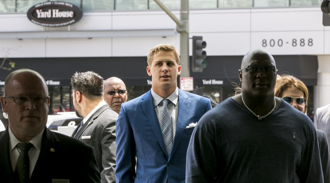 California's Jared Goff, center, is escorted by security staff as arrives for a news conference after being selected by the Los Angeles Rams as the first pick in the first round of the 2016 NFL football draft in Los Angeles, Friday, April 29, 2016. (AP Ph