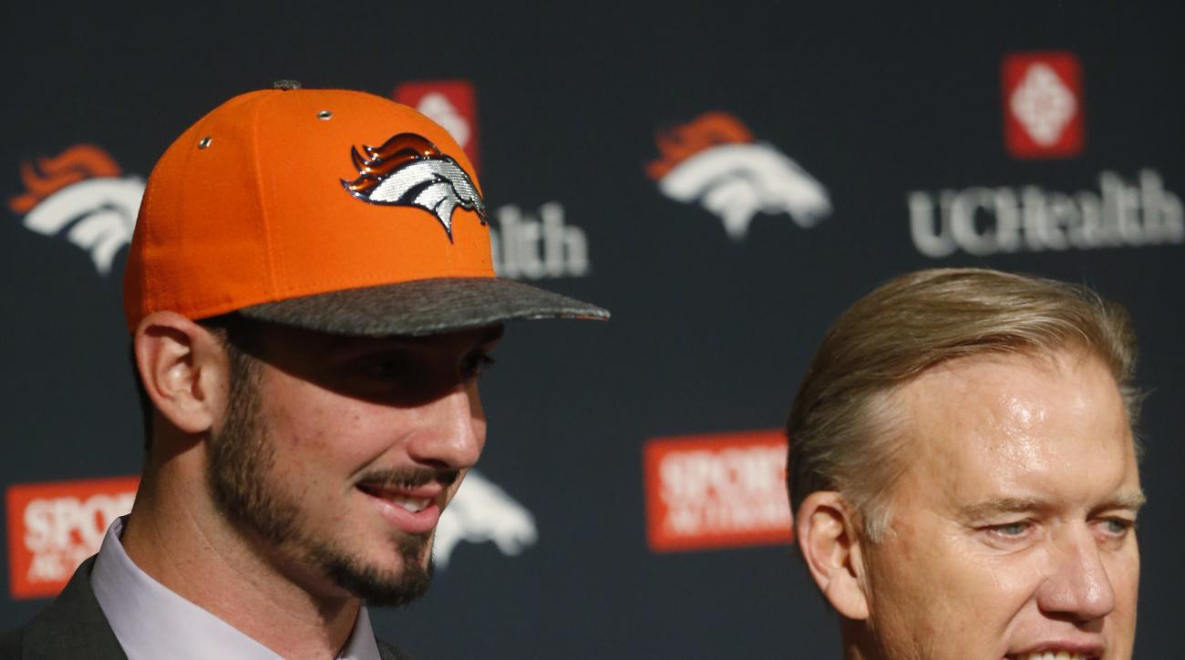 Denver Broncos first-round selection in the NFL football draft quarterback Paxton Lynch, left, from Memphis, holds his jersey with the help of team general manager John Elway as Lynch is introduced Friday, April 29, 2016, in the team's headquarters in Eng