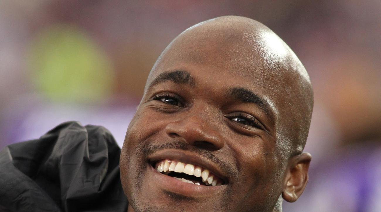 FILE - In this Aug. 22, 2015, file photo, Minnesota Vikings running back Adrian Peterson smiles on the sidelines during the first half of a preseason NFL football game against the Oakland Raiders in Minneapolis. Peterson is donating $100,000 toward relief