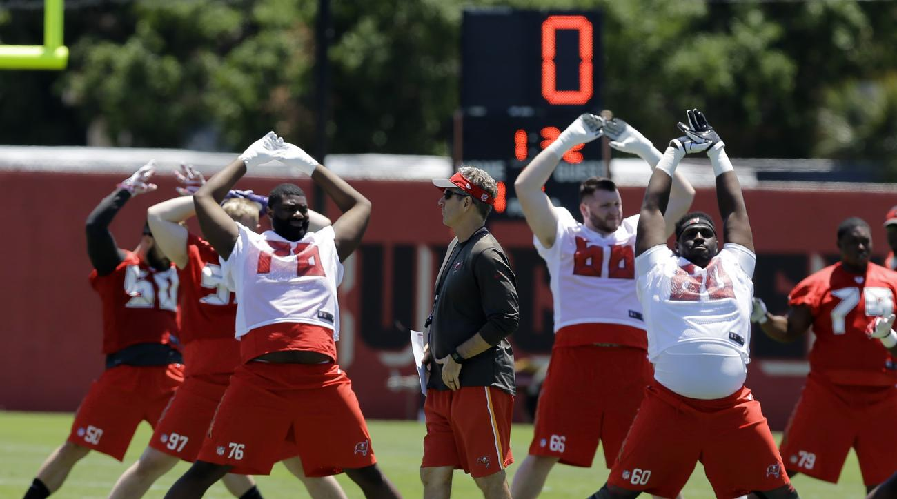Tampa Bay Buccaneers head coach Dirk Koetter, center, looks on a players stretch during a Buccaneers NFL football rookie minicamp Friday, May 6, 2016, in Tampa, Fla. (AP Photo/Chris O'Meara)
