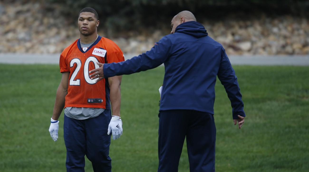 Denver Broncos rookie running back Devontae Booker, left, is instructed by running backs coach Eric Studesville during NFL football rookie camp football, Saturday, May 7, 2016, in the team's headquarters in Englewood, Colo. (AP Photo/David Zalubowski)