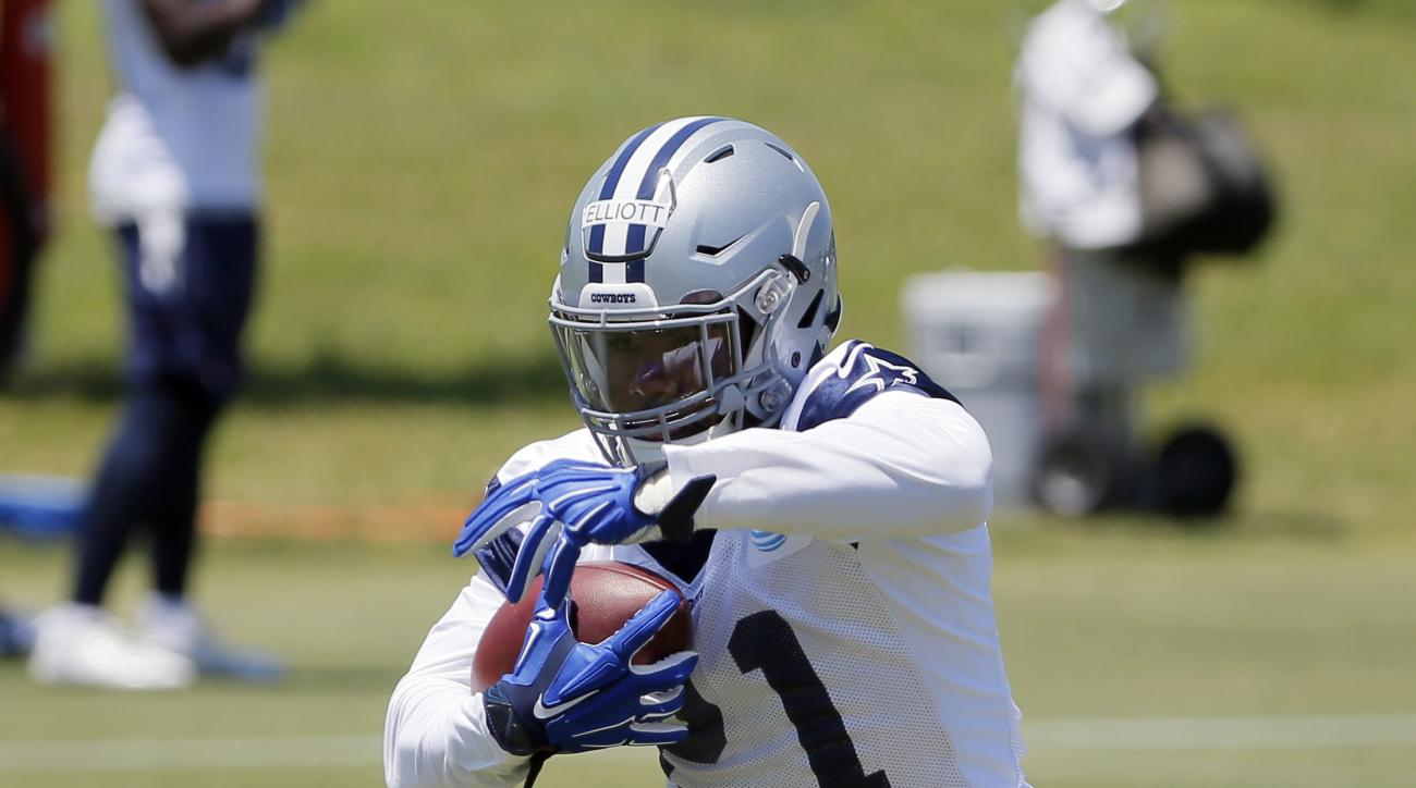 Dallas Cowboys running back Ezekiel Elliott carries the ball as he runs a drill during the team's NFL football minicamp, Saturday May 7, 2016, in Irving, Texas. (AP Photo/Tony Gutierrez)