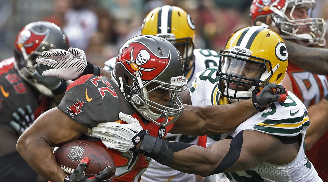 FILE - In this Sunday, Dec. 21, 2014 file photo, Tampa Bay Buccaneers running back Doug Martin (22) is stopped by Green Bay Packers inside linebacker Sam Barrington (58) during the third quarter of an NFL football game in Tampa, Fla. Barrington, a seventh