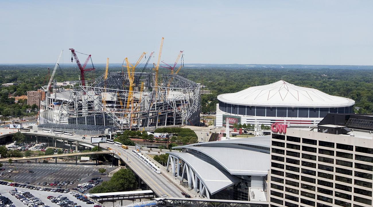 Mercedes-Benz Stadium, the future home of the Atlanta Falcons football team stands under construction, at left, next to the team's current stadium, the Georgia Dome, Monday, May 16, 2016, in Atlanta. Falcons owner Arthur Blank says the new stadium is on s