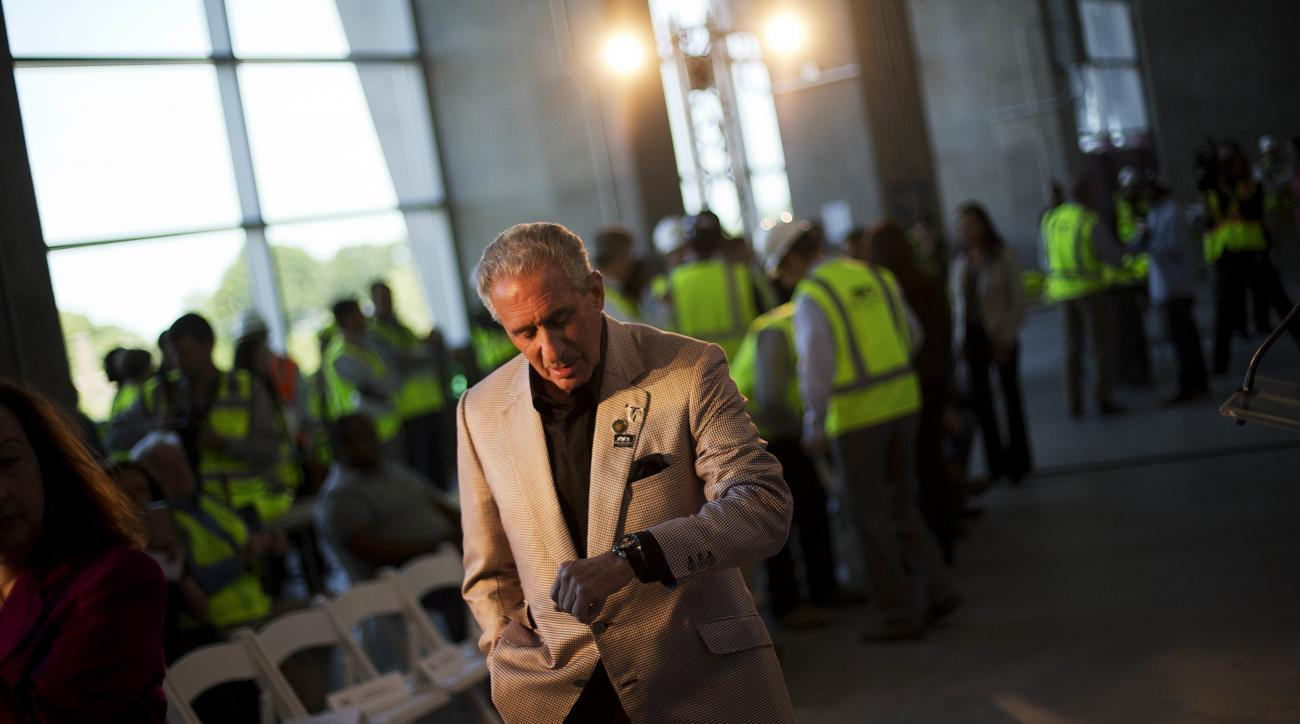 FILE - In this May 16, 2016, file photo, Atlanta Falcons owner Arthur Blank checks his watch before the start of a press event at the team's new stadium currently under construction in Atlanta. The 2019 Super Bowl is scheduled to be played at the new stad