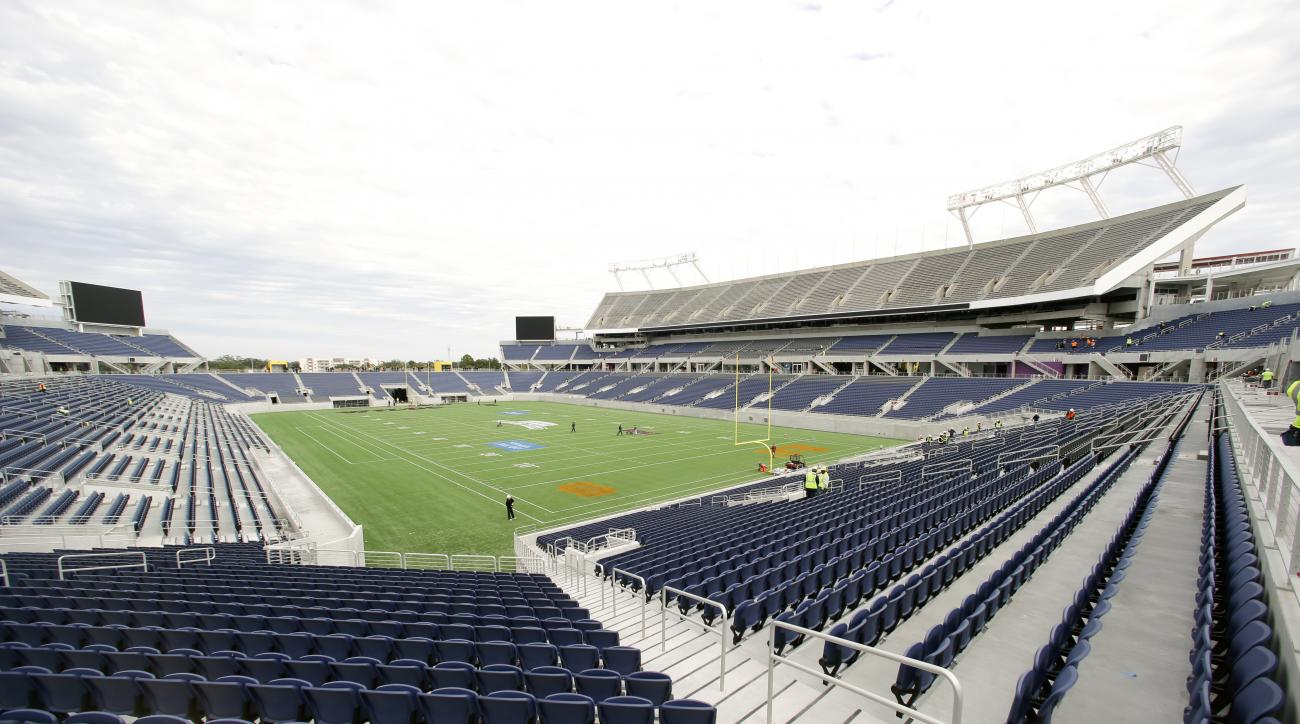 FILE - In this Nov. 19, 2014, file photo, grounds crew work on the football field at the new Citrus Bowl stadium in Orlando, Fla., Wednesday, Nov. 19, 2014. The NFL is moving the Pro Bowl from Honolulu to Orlando this season, three people with knowledge o