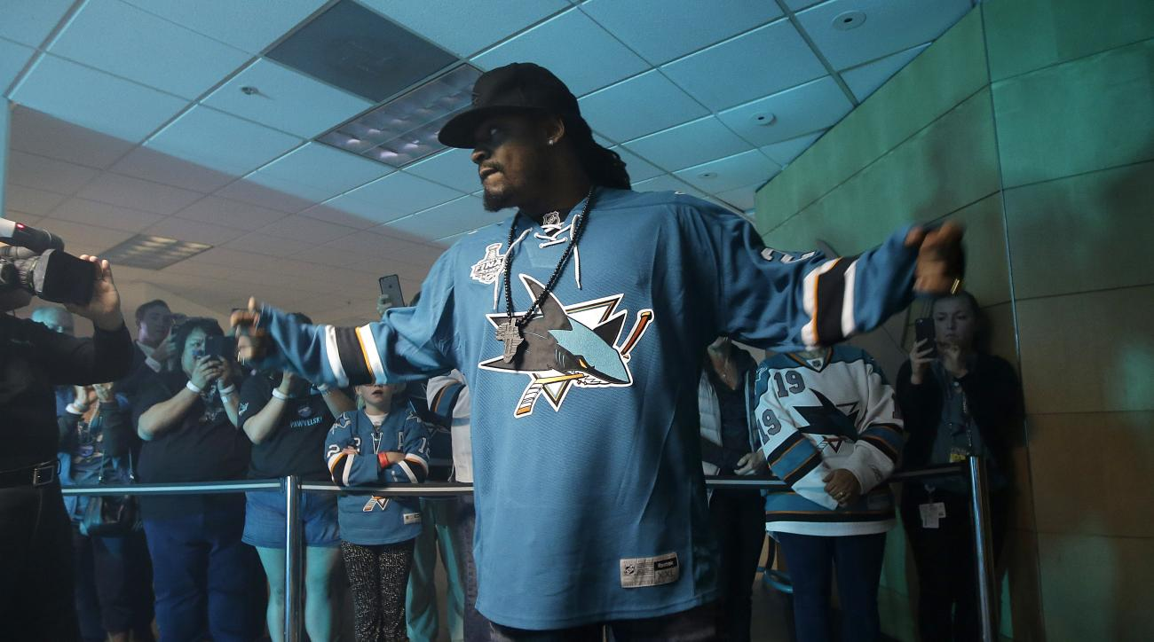 Former NFL football player Marshawn Lynch prepares to open a door for San Jose Sharks players to exit for the ice before Game 3 of the NHL hockey Stanley Cup Finals between the Sharks and the Pittsburgh Penguins in San Jose, Calif., Saturday, June 4, 2016