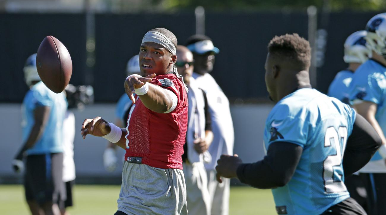 Carolina Panthers's Cam Newton, left, pitches the ball to Jonathan Stewart, right, during an NFL football practice in Charlotte, N.C., Tuesday, June 7, 2016. (AP Photo/Chuck Burton)
