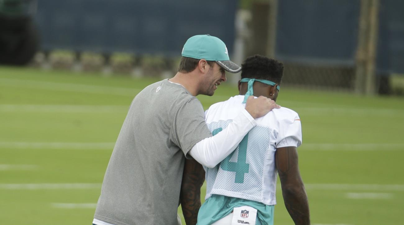 FILE - In this April 26, 2016 file photo, Miami Dolphins head coach Adam Gase, left, talks with wide receiver Jarvis Landry (14) during Miami Dolphins football voluntary veterans minicamp in Davie, Fla. In 2015, Landry set a franchise record with 110 rece