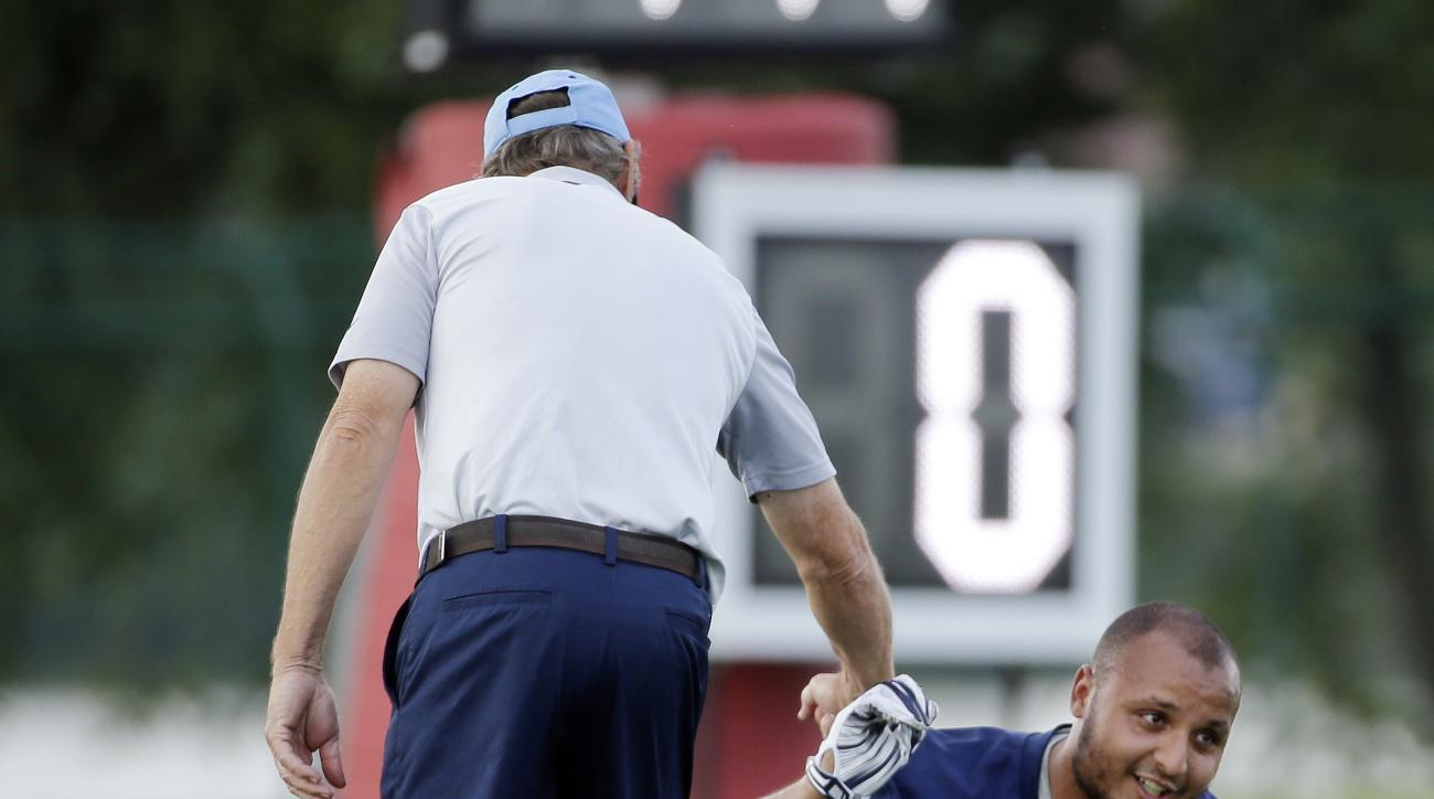 Tennessee Titans defensive coordinator Dick LeBeau, left, greets defensive end Mehdi Abdesmad (68) during an NFL football practice Tuesday, June 14, 2016, in Nashville, Tenn. (AP Photo/Mark Humphrey)
