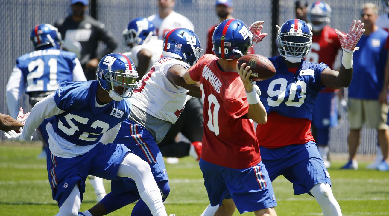 New York Giants outside linebacker Jonathan Casillas (52) and defensive end Jason Pierre-Paul (90) defend as quarterback Eli Manning (10) throws a pass during the NFL football team's minicamp, Wednesday, June 15, 2016, in East Rutherford, N.J. (AP Photo/J