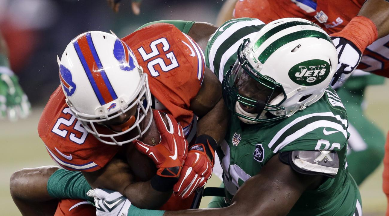 FILE - In this Nov. 12, 2015, file photo, Buffalo Bills running back LeSean McCoy, left, is hit by New York Jets defensive end Muhammad Wilkerson during an NFL football game in East Rutherford, N.J. Wilkerson is in a contract dispute with the team, unsure