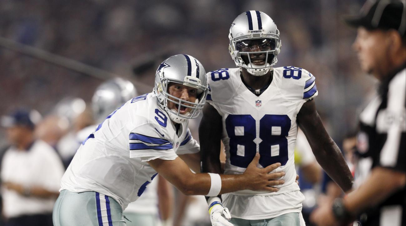 FILE - In this Sept. 13, 2015, file photo, Dallas Cowboys quarterback Tony Romo (9) and wide receiver Dez Bryant (88) react during the first half of an NFL football game against the New York Giants in Arlington, Texas. Both are anxious to get on the field