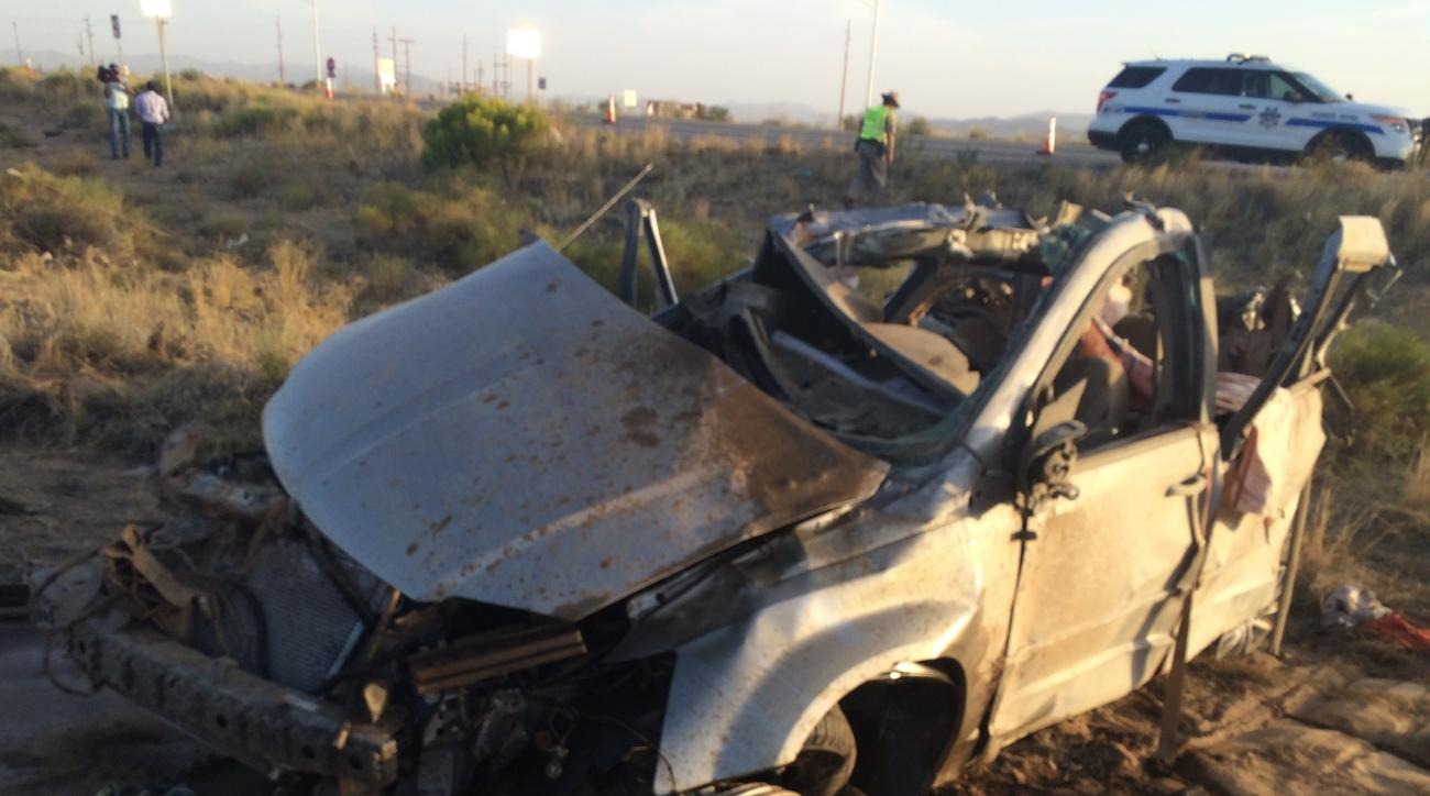 The wreckage of a van that collided with a Dallas Cowboys bus is seen near Kingman, Ariz., Sunday, July 24, 2016. Authorities said multiple people in the van died but nobody on the bus was seriously injured. (Barry White/KTNV via The AP)