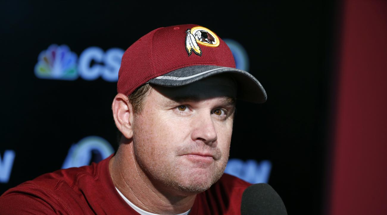 FILE - In this June 1, 2016 file photo, Washington Redskins head football coach Jay Gruden listens to a question during a media availability at the team's NFL football training facility at Redskins Park in Ashburn, Va. Theres no quarterback controversy at