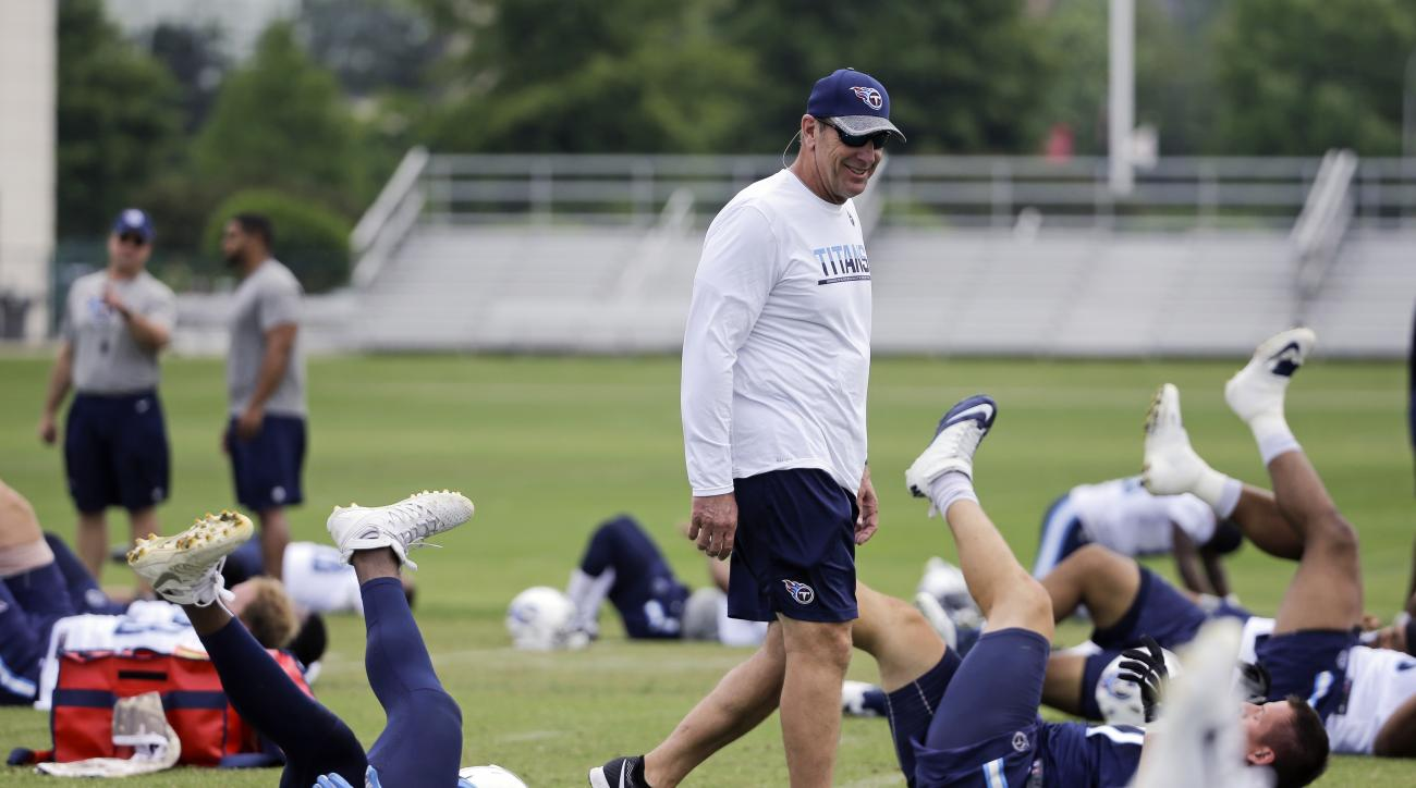 FILE - In this May 26, 2016, file photo, Tennessee Titans coach Mike Mularkey watches as players stretch during NFL football practice in Nashville, Tenn. Titans controlling owner Amy Adams Strunk saw enough of Mularkey as he finished the final nine games