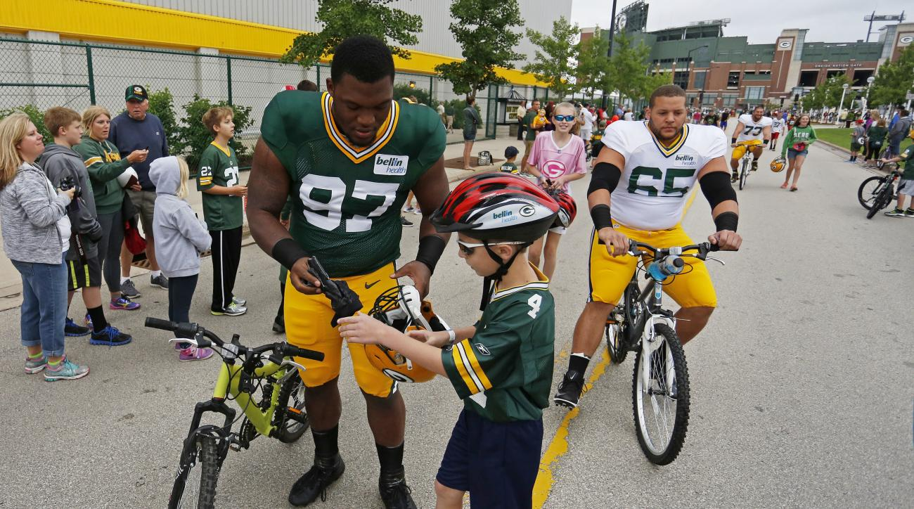 Green Bay Packers defensive tackle Kenny Clark (97) and guard Lane Taylor ride bikes to NFL football training camp, Thursday, July 28, 2016, in Green Bay, Wis. (AP Photo/Matt Ludtke)
