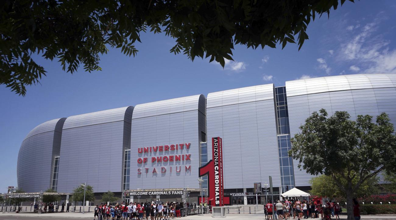 Arizona Cardinals fans line up outside University of Phoenix Stadium prior to the NFL football team's' training camp, Friday, July 29, 2016, in Glendale, Ariz. (AP Photo/Matt York)