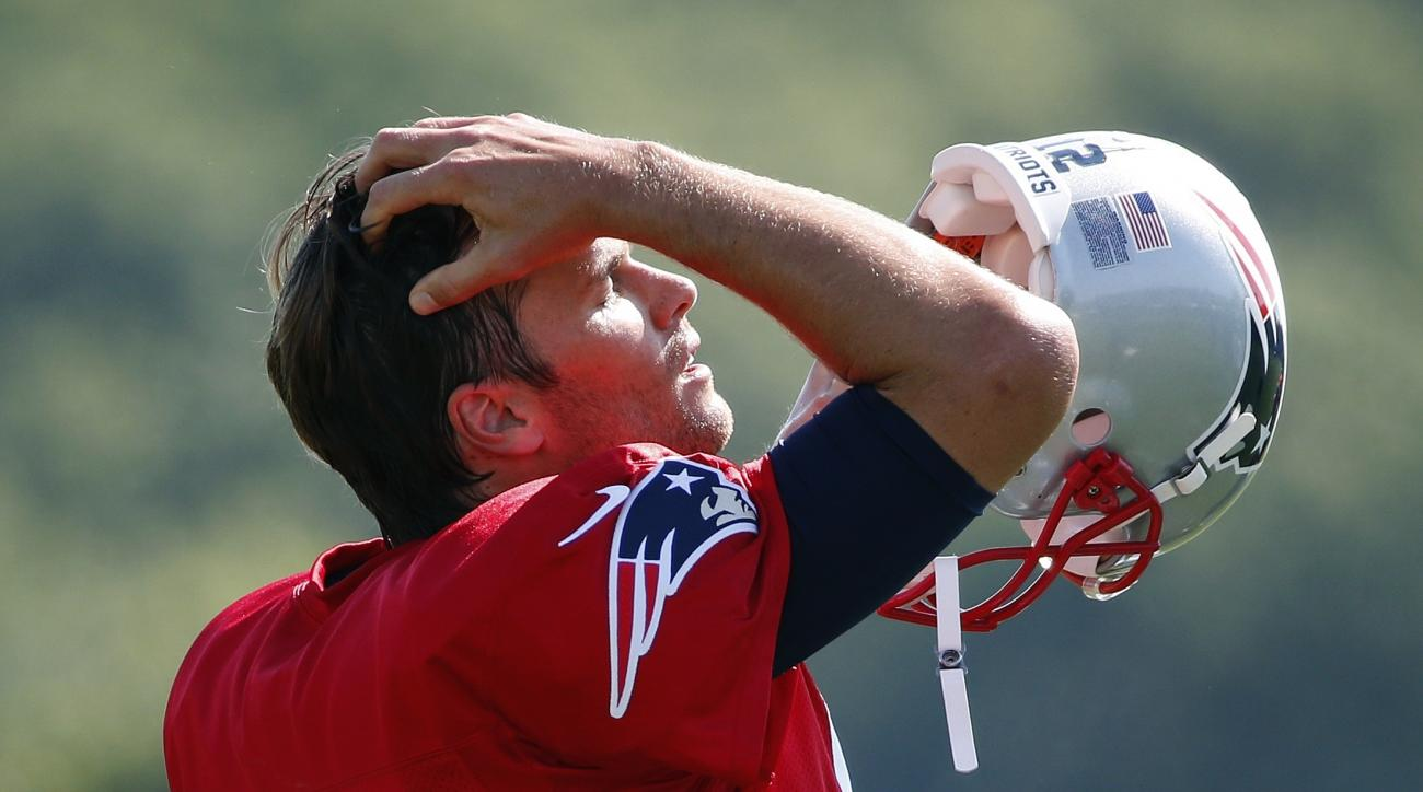 New England Patriots quarterback Tom Brady (12) dons his helmet during an NFL football training camp practice Saturday, July 30, 2016, in Foxborough, Mass. (AP Photo/Michael Dwyer)
