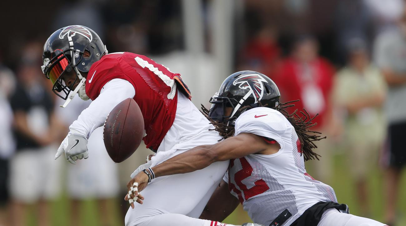 Atlanta Falcons cornerback Jalen Collins, right, breaks up a pass intended for wide receiver Eric Weems, left, during NFL football practice Saturday, July 30, 2016, in Flowery Branch, Ga. (AP Photo/John Bazemore)