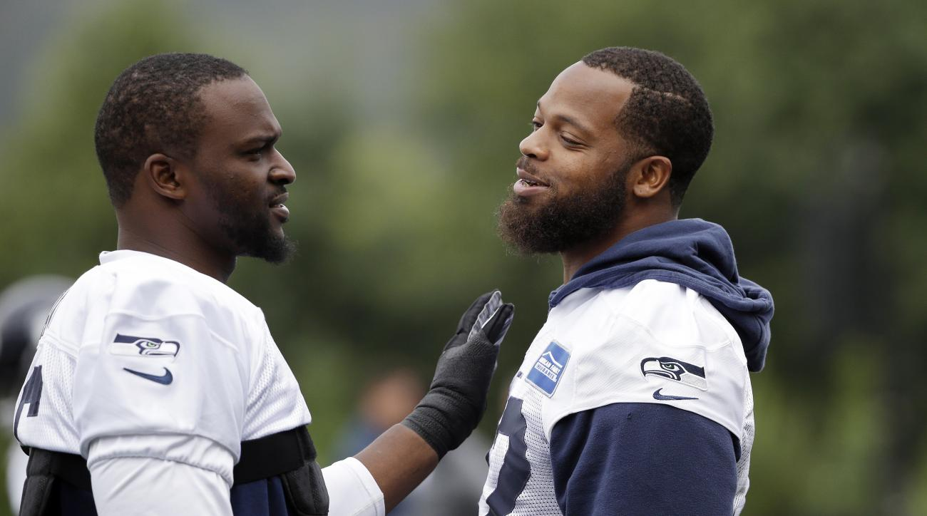 Seattle Seahawks' Michael Bennett, right, gets a pat from Cliff Avril during the team's NFL football training camp Saturday, July 30, 2016, in Renton, Wash. (AP Photo/Elaine Thompson)