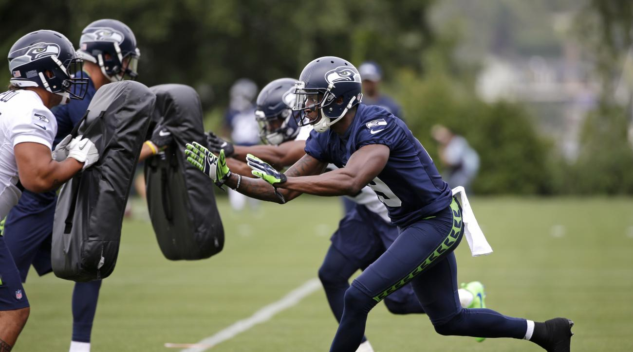Seattle Seahawks' Douglas McNeil, right, runs through a drill during the team's NFL football training camp Saturday, July 30, 2016, in Renton, Wash. (AP Photo/Elaine Thompson)