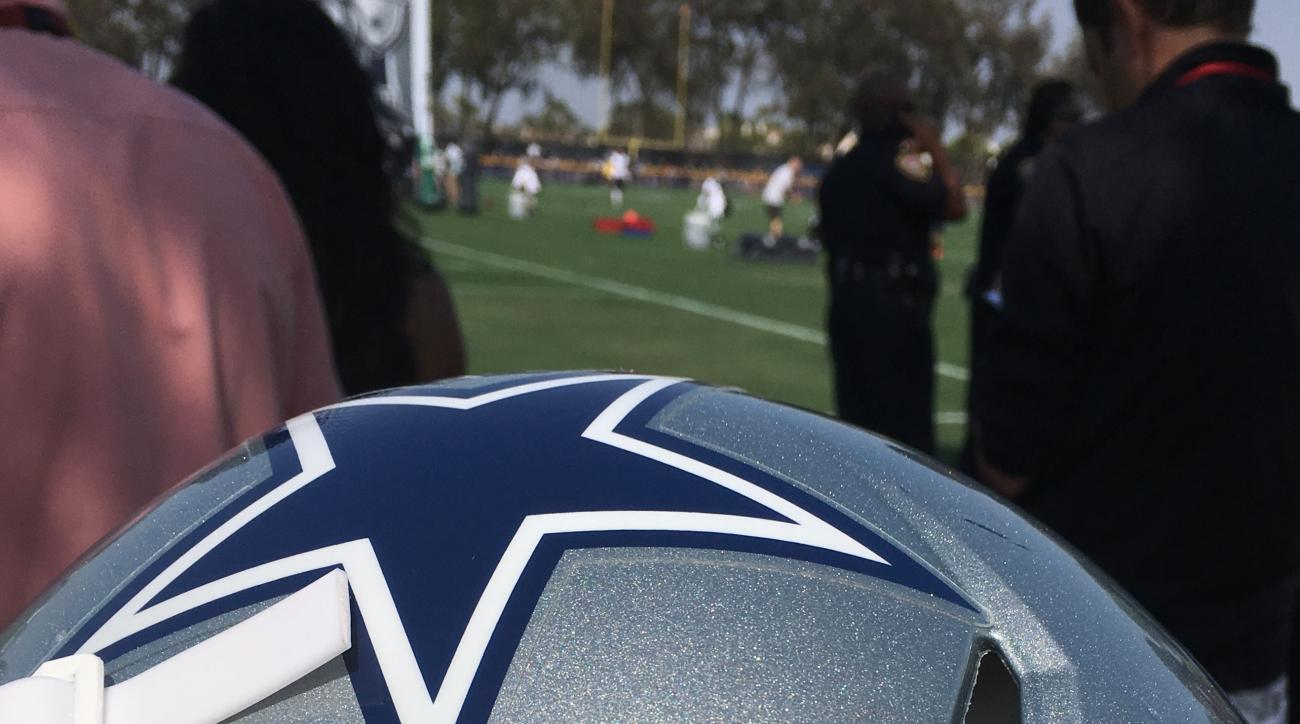 "An ""arm in arm"" decal is affixed to a Dallas Cowboys helmet at the NFL football team's training camp Saturday, July 30, 2016, in Oxnard, Calif. The Cowboys will wear the decal during preseason games, and possibly during the regular season. (AP Photo/Schuy"