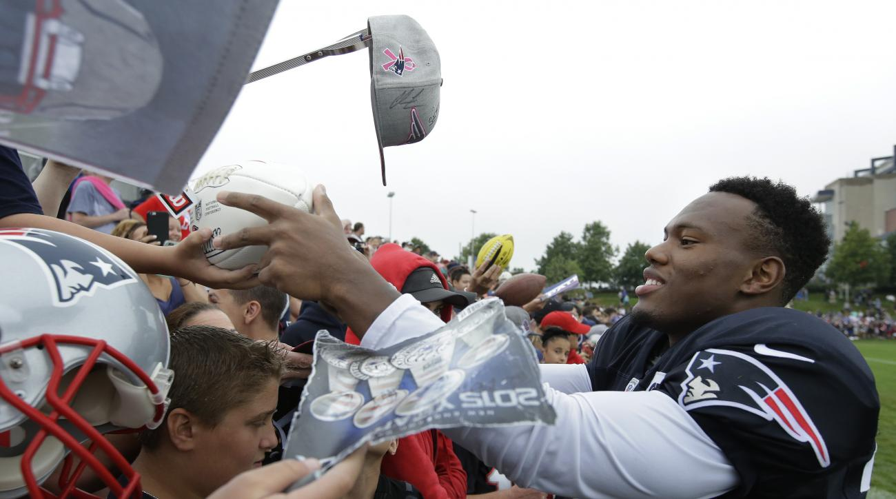 New England Patriots cornerback Cyrus Jones, right, gives autographs to fans following an NFL football training camp practice Sunday, July 31, 2016, in Foxborough, Mass. (AP Photo/Steven Senne)