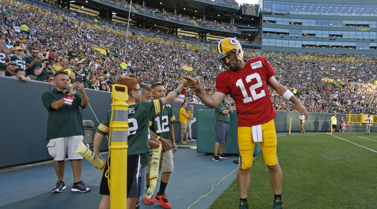 Green Bay Packers quarterback Aaron Rodgers high fives a fan on the sidelines during NFL football training camp, Sunday, July 31, 2016, in Green Bay, Wis. (AP Photo/Matt Ludtke)