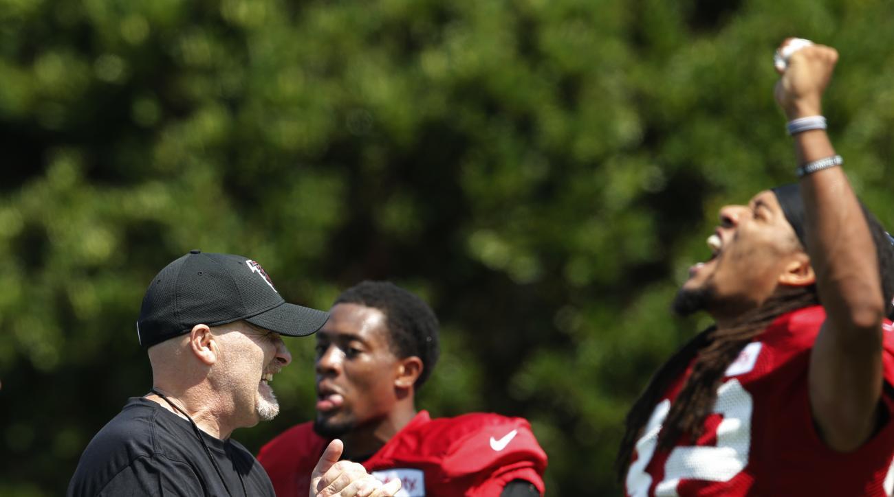 Atlanta Falcons head coach Dan Quinn smiles as his team takes the field after a break during an NFL football practice Tuesday, Aug. 2, 2016, in Flowery Branch, Ga. (AP Photo/John Bazemore)