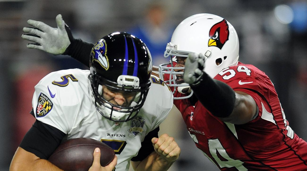 Baltimore Ravens quarterback (5) Joe Flacco tries to avoid being tackled by Arizona Cardinals linebacker (54) Dwight Freeney during a game played at University of Phoenix Stadium in Glendale, Ariz. on Monday, Oct. 26, 2015. (AP Photo/John Cordes)