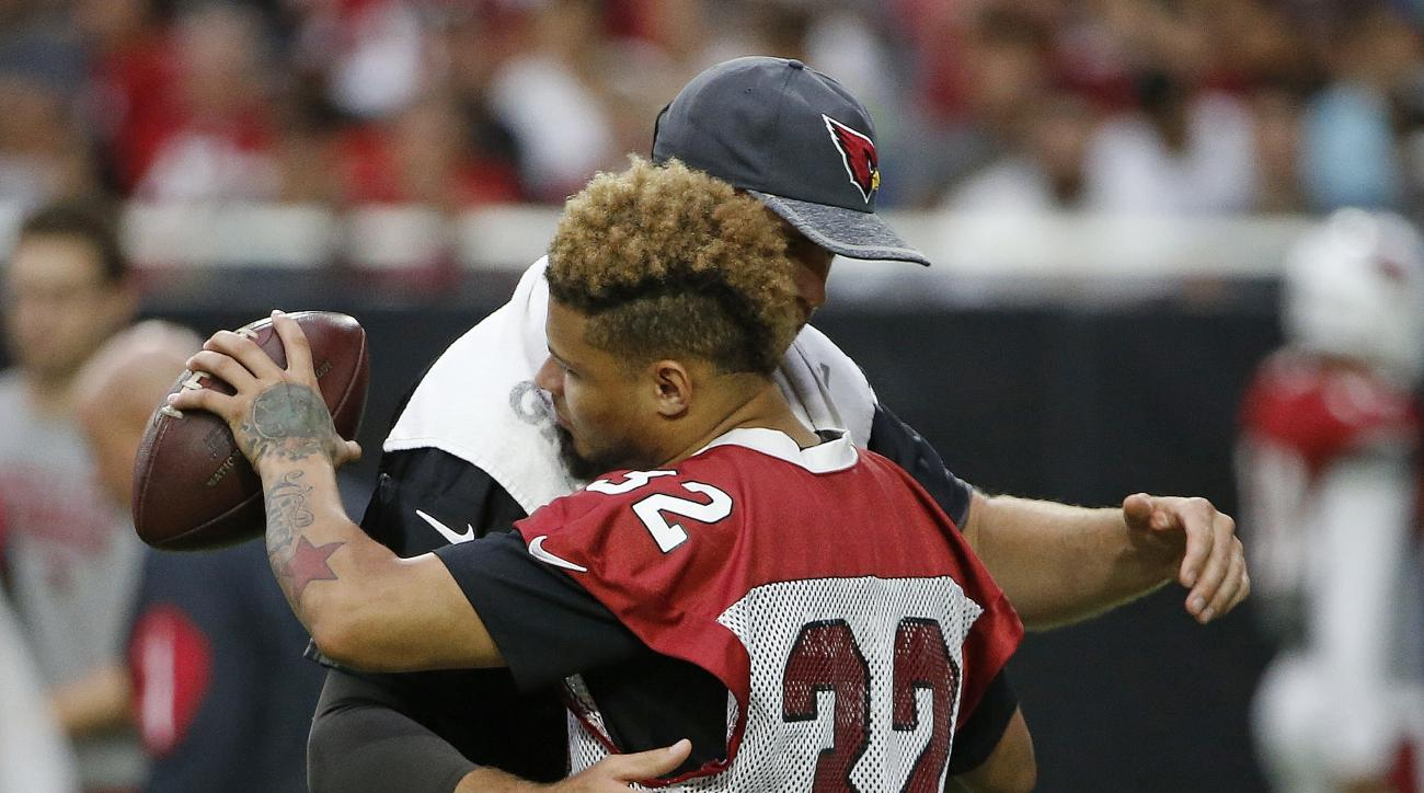 An injured Arizona Cardinals' Tyrann Mathieu (32) gets a hug from starting quarterback Carson Palmer during practice at the NFL football team's training camp Tuesday, Aug. 2, 2016, in Glendale, Ariz. The Cardinals and All-Pro defensive back Mathieu have a