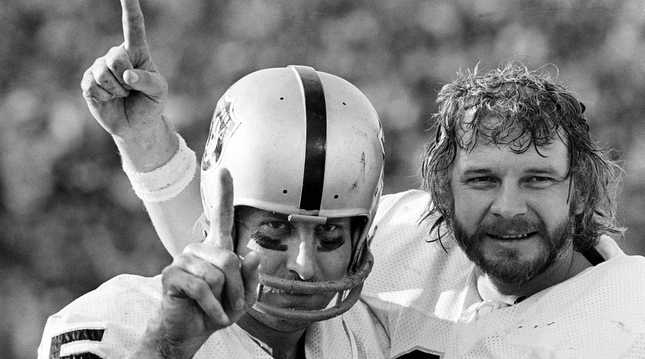 FILE - In this Jan. 9, 1977, file photo, receiver Fred Biletnikoff, left, and quarterback Ken Stabler of the Oakland Raiders proudly hold up one finger, indicating their team is No. 1, after defeating the Minnesota Vikings in the NFL football Super Bowl i