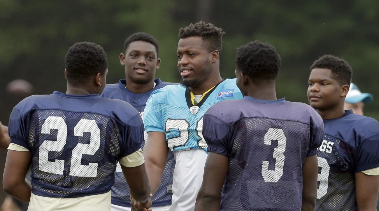 Carolina Panthers' Jonathan Stewart, center, greets members of the Spartanburg High School football team during an NFL training camp practice in Spartanburg, S.C., Thursday, Aug. 4, 2016. The high school participated in pre-practice stretching with the Pa