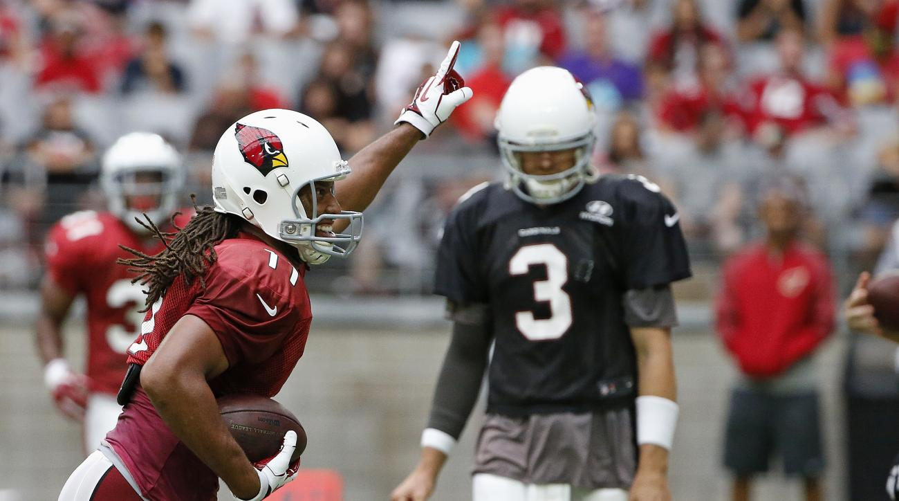 Arizona Cardinals' Larry Fitzgerald (11) celebrates a touchdown as he runs past quarterback Carson Palmer (3) during practice at the NFL football teams training camp Monday, Aug. 1, 2016, in Glendale, Ariz. (AP Photo/Ross D. Franklin)