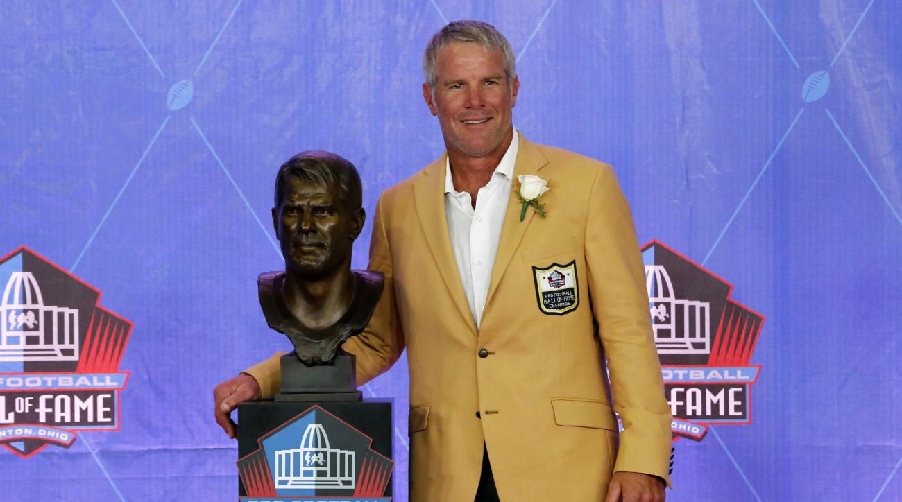 Former NFL player Brett Favre poses with a bust of himself during an induction ceremony at the Pro Football Hall of Fame, Saturday, Aug. 6, 2016, in Canton, Ohio. (AP Photo/Gene J. Puskar)