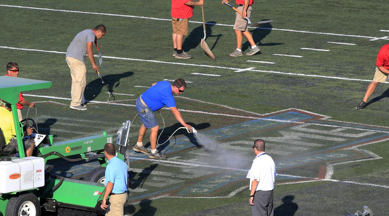 Crews clean the painted logo of the field at Tom Benson Hall of Fame Stadium before a preseason NFL football game between the Green Bay Packers and the Indianapolis Colts, Sunday, Aug. 7, 2016 in Canton, Ohio. (Cantonrep.com / Bob Rossiter)