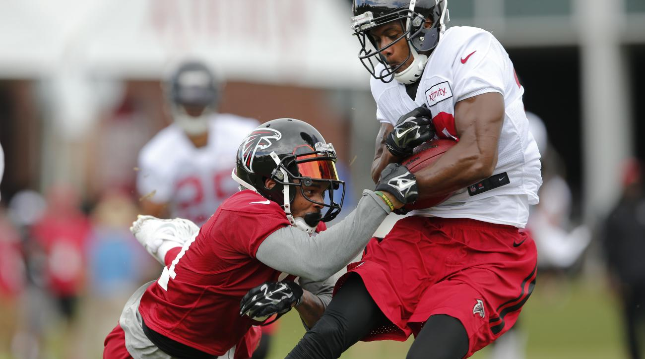 Atlanta Falcons wide receiver C.J. Goodwin (29) strips the ball away from wide receiver Eric Weems (14), left, during an NFL football training camp practice in Flowery Branch, Ga., Tuesday, Aug. 9, 2016, (AP Photo/John Bazemore)