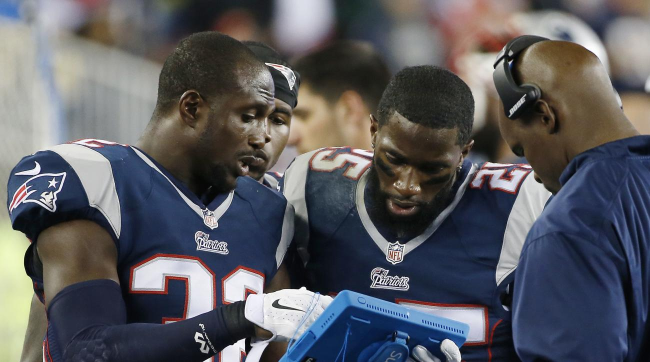 FILE - In this Oct. 16, 2014, file photo, New England Patriots defensive backs Devin McCourty (32) and Kyle Arrington (25) study a tablet device on the sideline in the second half of an NFL football game against the New York Jets, in Foxborough, Mass. The