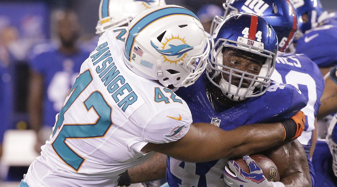 New York Giants running back Andre Williams (44) is stopped by Miami Dolphins linebacker Spencer Paysinger (42) during the second quarter of a preseason NFL football game, Friday, Aug. 12, 2016, in East Rutherford, N.J. (AP Photo/Ray Stubblebine)