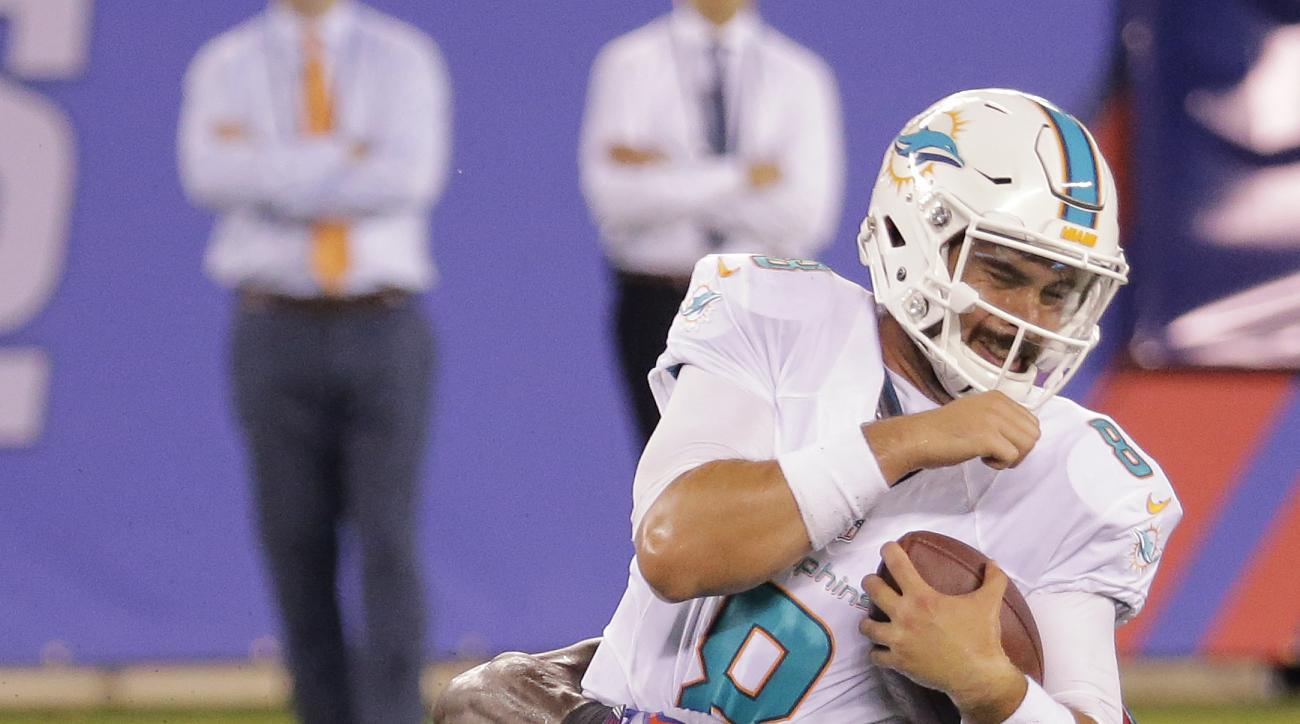 Miami Dolphins quarterback Matt Moore (8) is sacked by New York Giants defensive end Owa Odighizuwa (58) during the third quarter of a preseason NFL football game, Friday, Aug. 12, 2016, in East Rutherford, N.J. (AP Photo/Ray Stubblebine)